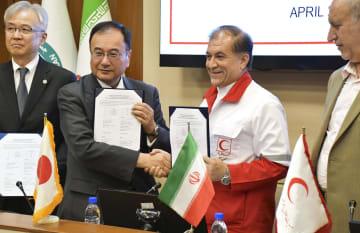 13日、テヘランで行われた支援物資の引き渡し式典で握手する斉藤貢・駐イラン大使(左から2人目)とイラン側の代表(共同)