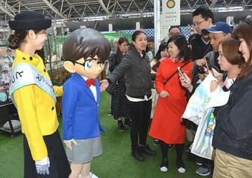 来場者との記念撮影に応じるコナン君と倉本さん=13日、大阪市北区の大阪ステーションシティ