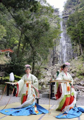 熊野那智大社で営まれた「桜花祭」で、那智の滝を背景に舞を奉納するみこ=14日、和歌山県那智勝浦町