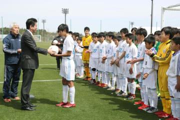 地元サッカーチームの選手にボールを手渡す安倍首相(左から2人目)=14日午前、福島県のJヴィレッジ(代表撮影)