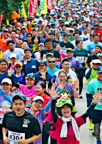 スタートの合図の後、一斉に駆けだすハーフマラソンの出場者たち=13日、伊江島・ミースィ公園(下地広也撮影)