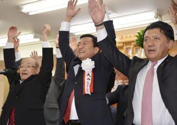 高松市長選で無投票当選が決まり、万歳をする大西秀人氏(中央)ら=14日