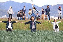 タマネギ畑の中で楽しそうにダンスする参加者ら=南あわじ市市新