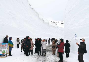 切り立つ雪の壁の景観を楽しむ観光客ら