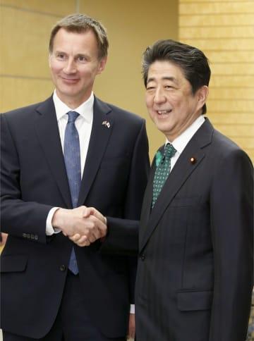 英国のハント外相(左)と握手する安倍首相=15日午前、首相官邸