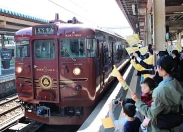 市民らの出迎えを受ける観光列車「ろくもん」=13日、上越市の直江津駅