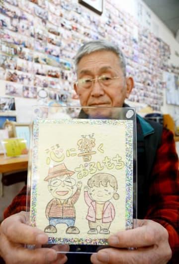 自殺を引き留められた女性が描いた似顔絵を持つ茂幸雄さん。「自殺の背景には社会のいろいろな問題がある」と話す=3月、福井県坂井市の東尋坊