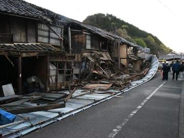 市道をふさぐ一部倒壊した長屋と鉄製の囲い=15日午後6時25分、関市宮地町