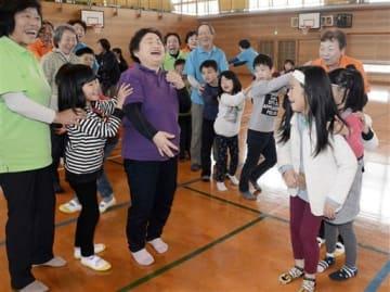 ゲームで交流する原町山遊倶楽部のメンバーと阿蘇西小の児童たち=阿蘇市