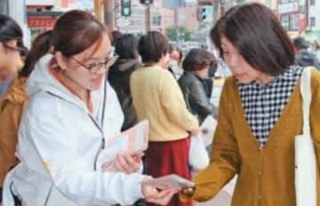 業務内容をまとめたリーフレットを配る法テラス大分の職員(左)