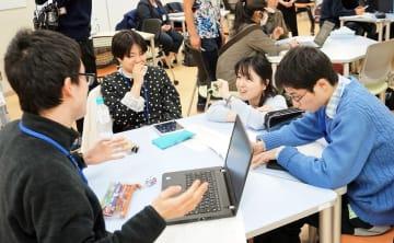 プレゼンテーションの準備で打ち合わせする学生ら。右から2人目は諏訪絵里子特任講師