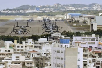 住宅地(手前)に隣接する米軍普天間飛行場=2016年11月、沖縄県宜野湾市