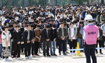 避難訓練を実施した熊本学園大で、熊本地震で犠牲となった大和晃さんを悼み黙とうする学生ら=16日、熊本市