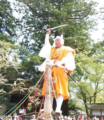 シイの木の柱に登って九字を切る山伏姿の保存会員=伊勢原市日向の日向薬師境内