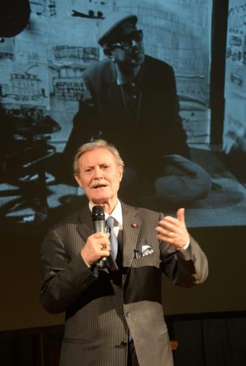 黒沢明監督の写真を背景に、映画「デルス・ウザーラ」撮影時の思い出を語るロシア国立マールイ劇場のソローミン芸術監督=15日、モスクワ(共同)
