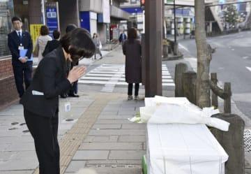 長崎市長だった伊藤一長氏が拳銃で撃たれた現場で、献花台に花を手向け手を合わせる市職員=17日午前、長崎市
