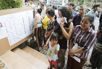17日、インドネシアのバリ島で、投票開始を前に列をつくる人たち(AP=共同)