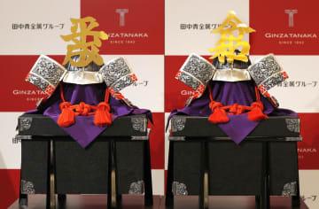 田中貴金属ジュエリーが名古屋市の店舗でお披露目した、平成と令和の文字を純金であしらった純銀のかぶと=17日午前
