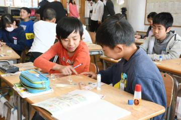 折り紙と日本の使用済み切手を使い、手紙と一緒に送るしおり作りもした児童たち=佐賀市の開成小