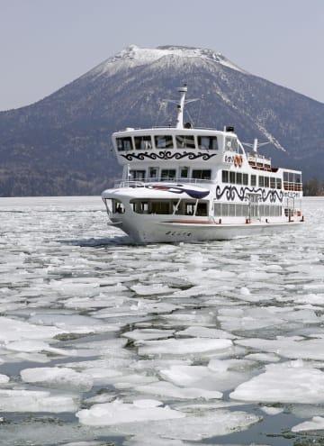 阿寒湖で湖面の氷を割って航路をつくる遊覧船「ましゅう丸」。奥は雄阿寒岳=17日、北海道釧路市