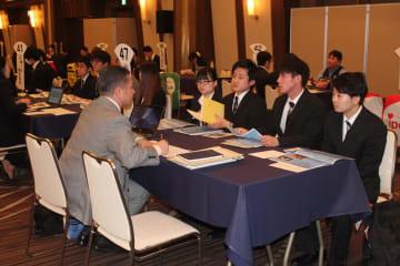 地元大学生らを対象にした青森県など後援の合同企業説明会。県内企業60社以上が参加し、採用担当者らが学生に事業内容などを説明していた=青森市内のホテル