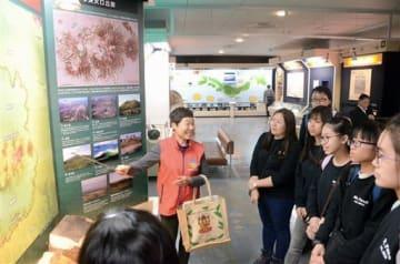 展示パネルを前に、カルデラの成り立ちや特徴についてガイドから説明を聞く香港の中学生たち=阿蘇市