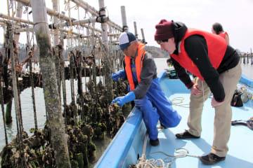 宮城県漁協関係者(左)から種ガキを育てる施設を説明される寄付者