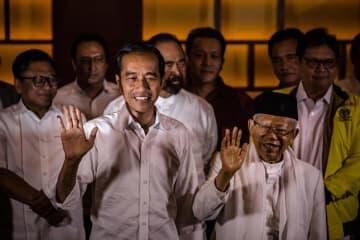 17日、インドネシアの首都ジャカルタでの記者会見で、手を振るジョコ大統領(手前左)と副大統領候補のマアルフ氏(同右)(ゲッティ=共同)