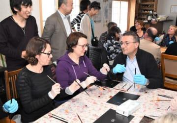 漆を使った装飾技法などを体験するアンドレ・ペラン会長(右)ら