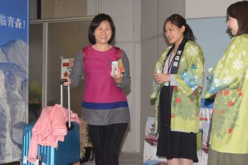 青森県職員らの歓迎を受け、笑顔を見せるチャーター便の乗客(左)=17日、青森空港
