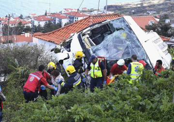 17日、ポルトガルのマデイラ島の観光バス横転現場で、対応に当たる救助隊員ら(AP=共同)