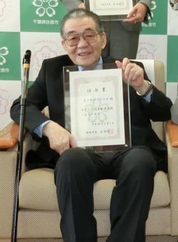 佐倉親善大使の任命書を手にするモンキー・パンチさん=2018年4月、佐倉市役所