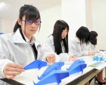 鯉をモチーフにした折り紙を制作する学生