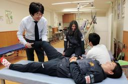 INAC神戸の福田ゆい選手(手前右)と談笑しながらリハビリを行う李潤煥さん(手前左)。中央奥は島袋奈美恵選手=東灘区住吉本町3
