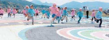 ジャンボこいのぼりの上を走る子どもたち=18日午前、玖珠町の玖珠川河川敷