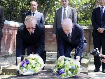 長崎市の稲佐悟真寺にあるオランダ人墓地で、献花する同国のヤコビ大使(右)とロシアのガルージン大使=18日午後
