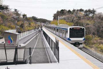 新駅と通過列車。サッカー日本代表がワールドカップ優勝時などにモニュメントを飾る台座(左)もある