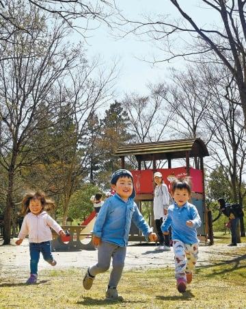 澄み渡る青空の下、元気に駆け回る子どたち=18日正午ごろ、仙台市泉区の七北田公園