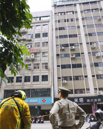 台湾東部を震源に起きた地震で、傾いたビル(右側)=18日、台北市(中央通信社=共同)