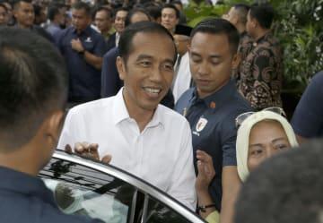 18日、インドネシアの首都ジャカルタで、与党連合の会合を終え笑顔を見せるジョコ大統領(中央)(AP=共同)