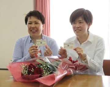 交付された「パートナーシップ宣誓証明書」を手に、ほほ笑む渡邉さん(右)と柿内さん =横須賀市職員厚生会館