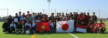 親善大会で各国の旗を手に笑顔を見せる選手たち=中津市永添の永添運動公園