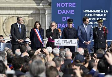 18日、パリで開かれたノートルダム寺院火災の消火活動で活躍した消防隊員らをたたえる式典。イダルゴ市長(左から2人目)らが出席した(ゲッティ=共同)
