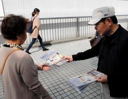 講演会のチラシを配る大森重美さん(右)=16日、JR川西池田駅前