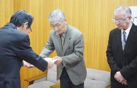 答申書を武田教育長に手渡す街道委員長(中央)