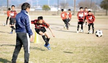 コーチ(手前)の指導のもと、シュート練習するロアッソ熊本ジュニアユース阿蘇の選手たち=阿蘇市農村公園あぴか