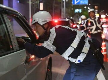 ドライバーの呼気を調べる警官=17日夜、豊中市寺内の国道423号