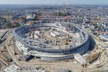 屋根工事やメインスタンド側(右)のVIPラウンジ工事が進む新スタジアム建設現場=18日午前8時40分、宇都宮市西川田2丁目、小型無人機から