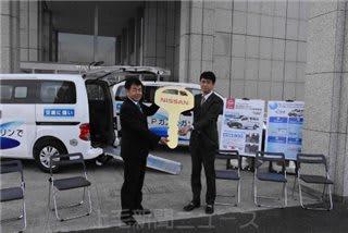 日産自動車の担当者からマスコットキーを受け取る山田会長