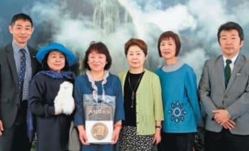 友人と一緒に古代アンデス文明展を訪れ、2万人突破の記念品を手にする江藤武子さん(左から3人目)=19日午前、県立美術館